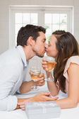 Loving young couple kissing with wine glasses — ストック写真