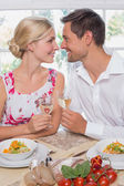 Loving couple with wine glasses looking at each other at dining — Stock Photo