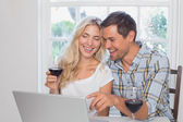 Couple with wine glasses using laptop at home — Stock Photo