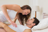 Woman sitting on man in bed — Stockfoto