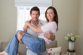Smiling man carrying woman at home — Stock Photo