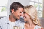 Loving couple with champagne flutes at home — Stock Photo