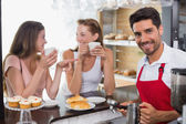 Women drinking coffee with barista at counter in coffee shop — Stockfoto