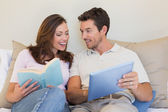 Happy couple with laptop and book on couch — Stock Photo