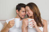 Happy relaxed couple with coffee cups — Stock Photo