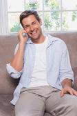 Casual man using mobile phone on sofa — Stock Photo