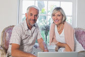 Smiling mature couple using laptop at home — Stok fotoğraf