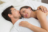 Loving young couple lying in bed at home — Stock Photo