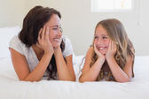 Mother and daughter looking at each other while in bed — 图库照片