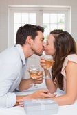 Loving young couple kissing with wine glasses — 图库照片