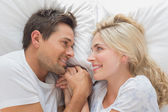 Loving couple looking at each other while lying in bed — Stock Photo