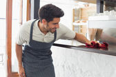 Waiter cleaning countertop with sponge — Stock Photo