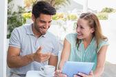 Glückliches paar mit kaffeetasse mit digitalen tablet im café — Stockfoto