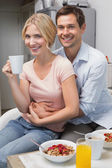 Man embracing woman at breakfast table at home — ストック写真