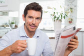 Man with newspaper and coffee cup at home — Foto de Stock