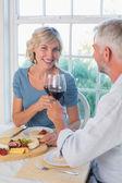 Mature couple toasting wine glasses over food — Stock Photo