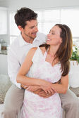 Loving man embracing woman from behind at home — 图库照片