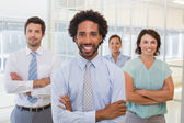 Smiling young businessman with colleagues in office — Stock Photo