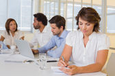 Businesswoman writing notes with colleagues in meeting at office — Stock Photo
