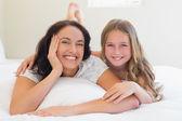 Žena a dcera leží vedle sebe v posteli — Stock fotografie