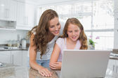 Happy mother and daughter using laptop in kitchen — Stock fotografie