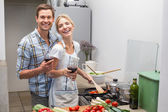 Loving young couple with wine glass in kitchen — Stock Photo