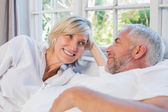 Smiling relaxed mature couple lying in bed at home — Stock Photo