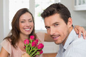Close-up of a happy man and woman with flowers — Stock Photo