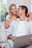 Happy casual couple using laptop in living room — Stock Photo