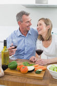 Cheerful couple with wine glasses in kitchen — Stock Photo