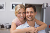 Smiling woman embracing man from behind in kitchen — Stock Photo