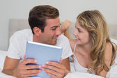 Smiling couple using digital tablet in bed — Stock Photo