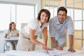Happy colleagues working on blueprints in office — Stock Photo