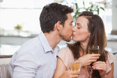 Loving couple with wine glasses kissing — Stock Photo