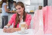 Femme souriante, à l'aide de téléphone portable dans le café-restaurant — Photo