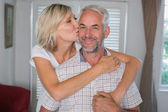 Happy woman embracing and kissing mature man — Stock Photo