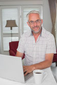 Smiling mature man using laptop at home — Stock fotografie
