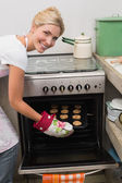 Smiling woman putting a tray of cookies in oven at kitchen — Stock Photo
