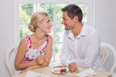 Loving couple with pastry looking at each other at dining table — Stock Photo