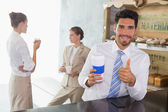 Businessman with coffee sipper gesturing thumbs up — Stock Photo