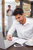 Homme qui rédige des notes avec l'ordinateur portable dans le café-restaurant — Photo