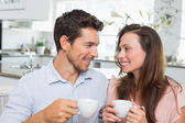 Happy couple with coffee cups in kitchen — Stock Photo