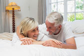 Happy mature couple lying in bed at home — Stock Photo