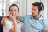 Couple with mobile phone and headphones in living room — Stock Photo