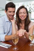 Happy woman showing engagement ring besides man — Stock Photo