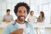 Smiling businessman having coffee with colleagues in background — Stock Photo