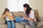 žena ukazuje na vyděšená dcera na pohovce — Stock fotografie
