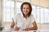 Smiling businesswoman working on blueprint in office — Stock Photo