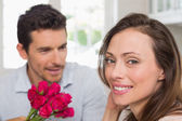 Happy woman and man with flowers at home — Foto Stock