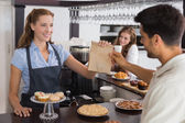 Cafe owner giving packed food to a couple at coffee shop — Stockfoto